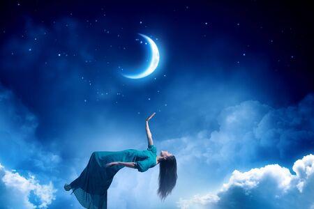 Dreamy beautiful woman in green dress flying in sky
