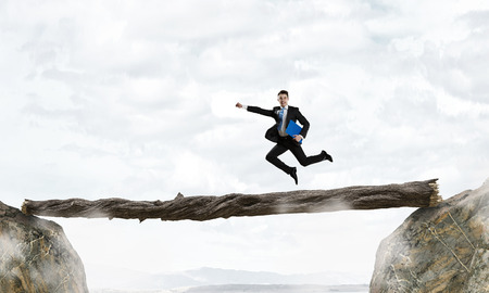 Young successful businessman running on log above gap. Risk and challenge concept