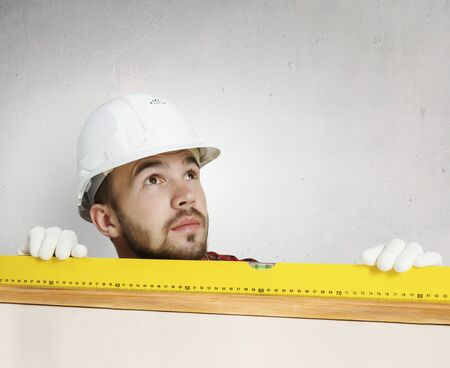 Young handsome man in hardhat with measure level