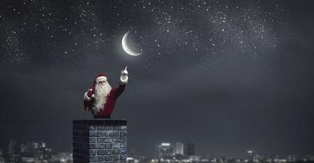 Santa on house roof inside brick chimney pointing with finger Zdjęcie Seryjne