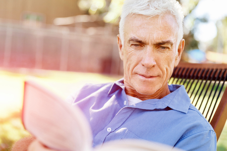 Handsome senior sitting in park and reading book