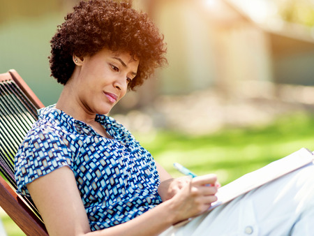 authors: Beautiful young woman writing in her diary in summer park
