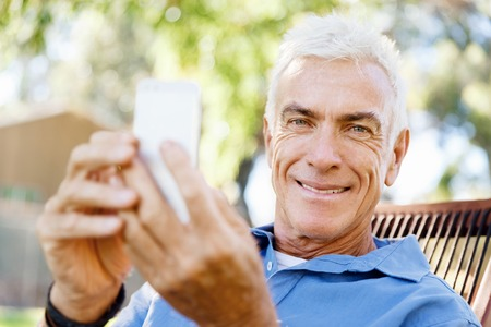 Handsome senior man outdoors using mobile phone