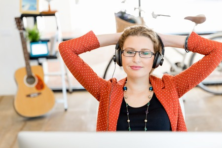 break from work: Young woman in casual clothes in an office with headphones Stock Photo