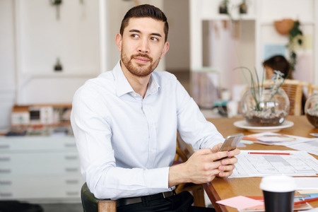 Young businessman sitting at desk in office with mobile phone