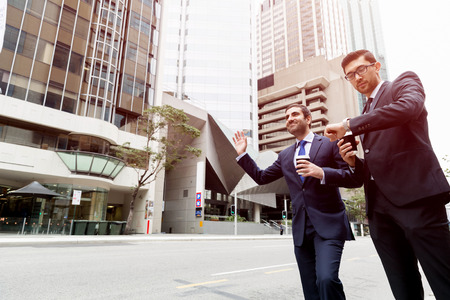 Two young businessmen in suits catching taxi