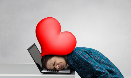 Stressed woman with head under pressure of red heart