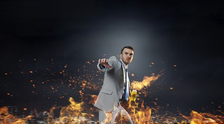 man power: Young aggressive businessman throw burning molotov cocktail