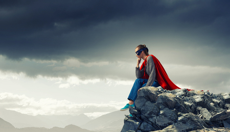 Junge attraktive Frau in der Maske und roten Umhang auf Felsen oben Standard-Bild - 65860208