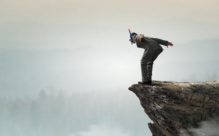 risky job: Businessman in suit and diving mask jumping from rock top