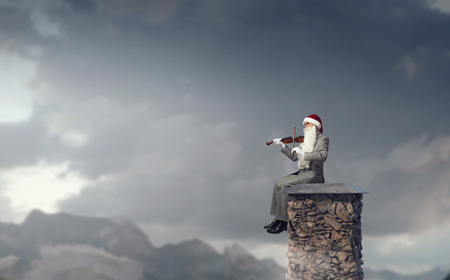 soloist: Businessman in Santa hat and beard playing violin Stock Photo