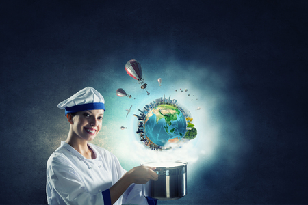 Young attractive cook woman making magic above pan. Elements of this image are furnished by NASA Banco de Imagens