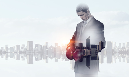 Businessman in boxing gloves against cityscape background Stock Photo