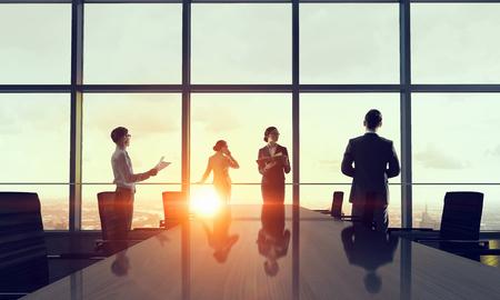 reuniones empresariales: Grupo de hombres de negocios a la luz de la salida del sol contra el ventanal. Medios compuestos Foto de archivo