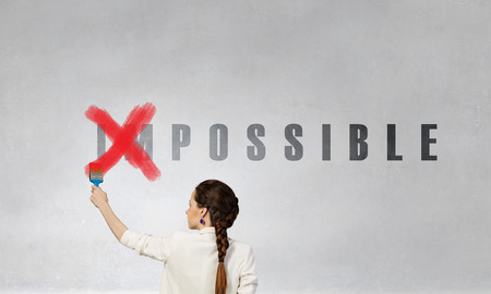 Woman changing word impossible in to possible by erasing part of word with paint roller Фото со стока