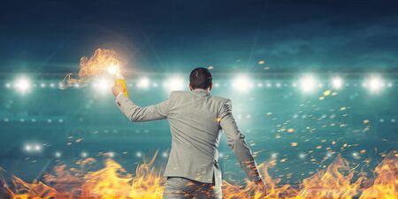 Young aggressive businessman throw burning molotov cocktail. Mixed media Stock Photo