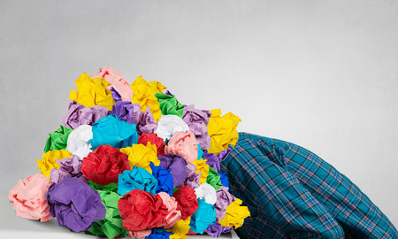 Stressed woman with head under heap of paper balls Stock Photo