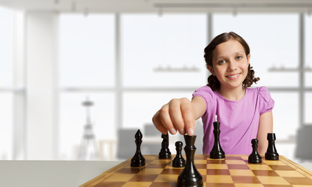 Smart cute kid girl playing chess game. Mixed media
