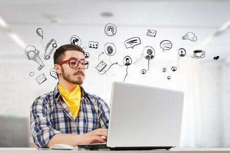 Young man in glasses and checked shirt working on laptop. Mixed media Stock Photo