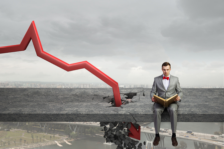 Businessman read book and red arrow destroying concrete barrier