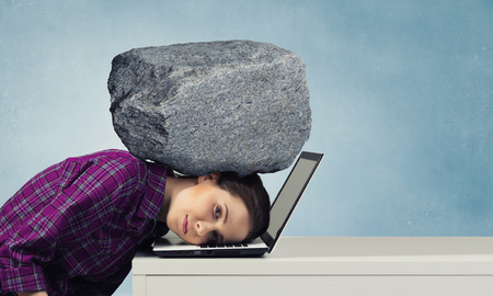 oppressed: Stressed woman with head under pressure of big stone