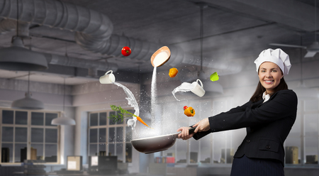 woman handle success: Young businesswoman in cook hat with pan in hand. Mixed media Stock Photo