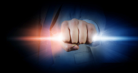 money cosmos: Hand of businessman holding in fist glowing light Stock Photo
