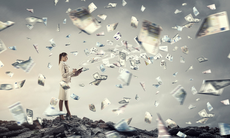 money flying: Empresaria al aire libre con dinero volando fuera del libro