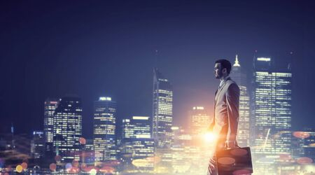 Elegant businessman with suitcase walking against night city background