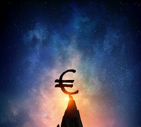 Silhouette of euro symbol on peak of rock