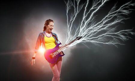 rocker girl: chica de la roca atractiva joven que toca la guitarra eléctrica