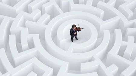 Young businessman in white labyrinth playing violin Stock Photo