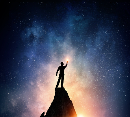 Silhouette of businessman against night starry sky Фото со стока