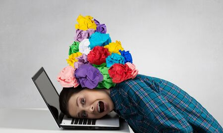 suppressed: Stressed woman with head under heap of paper balls Stock Photo
