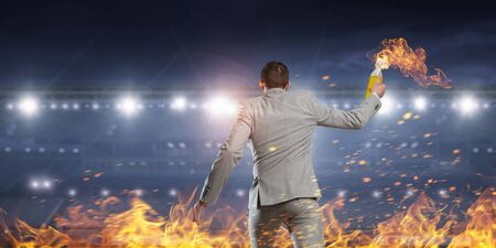 sabotage: Young aggressive businessman throw burning molotov cocktail. Mixed media Stock Photo