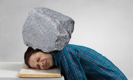 Stressed woman with head under pressure of big stone