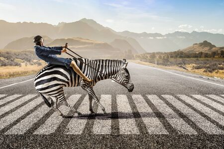 Young pretty fearless woman riding zebra animal Stock Photo