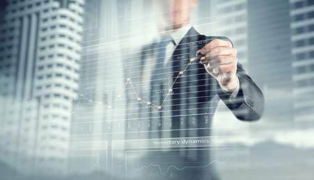 Exposure image of businessman drawing graph on screen. Mixed media
