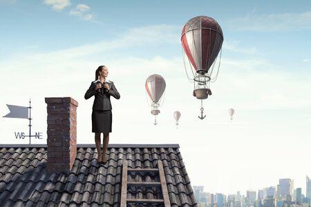 Career woman on roof looking in binoculars over city