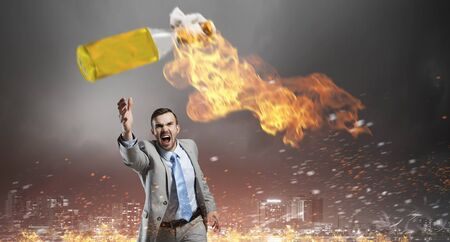 Young aggressive businessman throw burning molotov cocktail