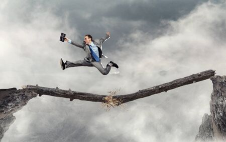 impediment: Young successful businessman jumping over gap. Risk and challenge concept