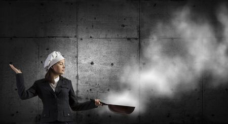 woman handle success: Young businesswoman in cook hat with pan in hand