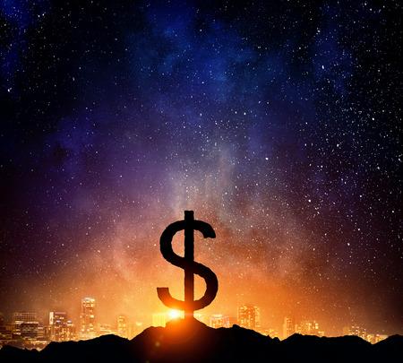 Silhouette of dollar symbol on peak of rock