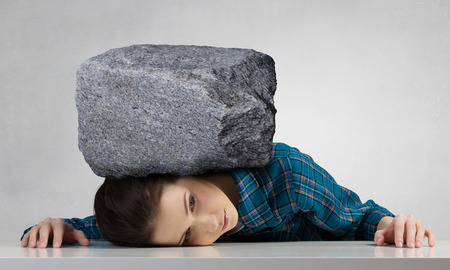 suppressed: Stressed woman with head under pressure of big stone