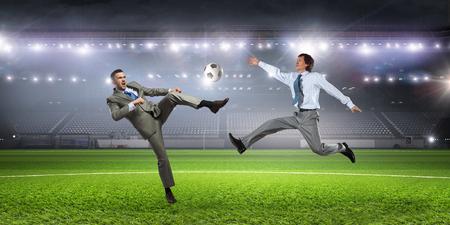 kicking ball: Businessman in suit at soccer field kicking ball. Mixed media