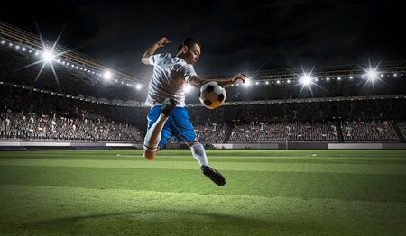 Soccer player with ball in action at stadium. Mixed media