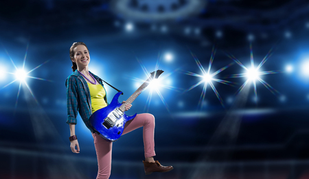 Young attractive rock girl playing electric guitar. Mixed media