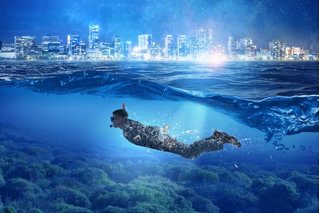 Businessman in suit and diving mask swiming under water