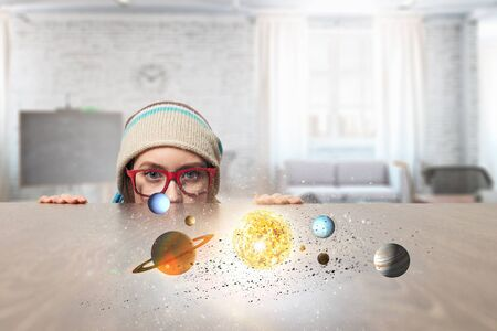 Hipster girl looking from under table. Mixed media Stock Photo