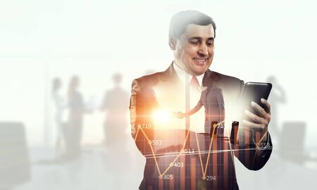Double exposure of city and businessman with digital tablet. Mixed media